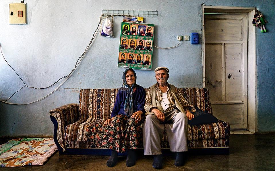 Αλεβίτες αγρότες κουρδικής καταγωγής στο σπίτι τους στην πόλη Καχραμανμαράς, όχι μακριά από τα σύνορα με τη Συρία. Είναι η πόλη όπου το 1978 καταγράφηκε η μαζική σφαγή Αλεβιτών από τους Γκρίζους Λύκους. Πάνω από το ηλικιωμένο ζευγάρι διακρίνεται εικόνισμα των 12 ιμάμηδων, εκ των οποίων πρώτος είναι ο Αλί. © Νίκος Πηλός