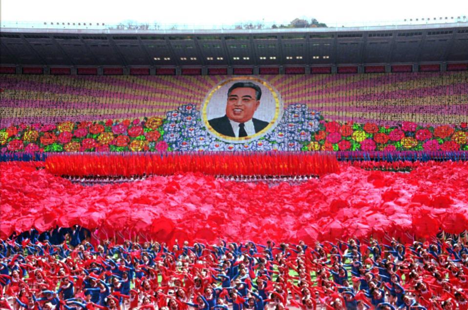 Χιλιάδες παιδιά στη Βόρεια Κορέα χορεύουν και κρατούν χρωματιστές καρτέλες, σχηματίζοντας την εικόνα του Κιμ Ιλ Σουνγκ, του ιδρυτή του βορειοκορεατικού κράτους, σε συλλαλητήριο στην Πιονγιάνγκ, το 1995. (AP Photo/John Leicester)