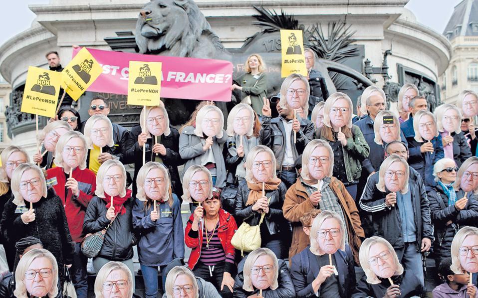 Η Ε.Ε. χρειάζεται βαθιά μεταρρύθμιση, αν δεν θέλει να αντιμετωπίσει το ενδεχόμενο του Frexit, δηλαδή της εξόδου της Γαλλίας, τόνισε χθες ο κεντρώος υποψήφιος για την προεδρία, Εμανουέλ Μακρόν. Στη φωτογραφία, ακτιβιστές διακωμωδούν το Εθνικό Μέτωπο κατά τον εορτασμό της Εργατικής Πρωτομαγιάς στο Παρίσι, εμφανίζοντας τον ιδρυτή του ακροδεξιού κόμματος, Ζαν- Μαρί Λεπέν, με την κόμη της κόρης του.