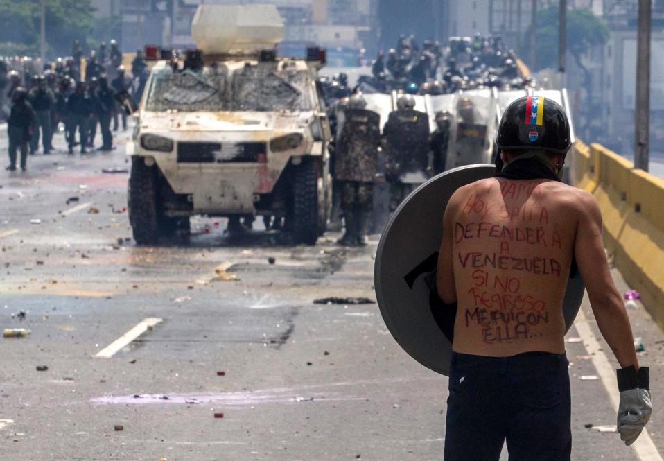 Μαμά, αν αργήσω... Για έναν ολόκληρο μήνα, άνθρωποι κάθε ηλικίας βρίσκονται στους δρόμους του Καράκας, δίνοντας δυναμικό παρών και μετρώντας απώλειες σε ανθρώπινες ζωές, καθώς μάχονται για το μέλλον τους και το μέλλον της χώρας τους. Τους 39 έφτασε ο αριθμός των νεκρών, χωρίς να υπάρχει κάποια εξέλιξη που να προοιωνίζει ένα τέλος. Δικαίως λοιπόν ο νεαρός της φωτογραφίας έγραψε στο μήνυμα στην πλάτη του «Μαμά, σήμερα βγήκα για να υπερασπιστώ την Βενεζουέλα. Αν δεν γυρίσω, θα είμαι μαζί της». EPA/CRISTIAN HERNANDEZ