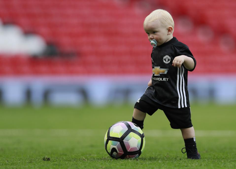 Γιορτή. Τελείωσε το ματς μεταξύ Manchester United και Crystal Palace και το γήπεδο του  Old Trafford γέμισε παιδιά. Οι ποδοσφαιριστές γιόρτασαν με γιους και κόρες, με τα παιδιά να παίρνουν μια μικρή δόση από τη «δουλειά» του μπαμπά. Στη φωτογραφία, ο Kit Rooney, ο μικρότερος γιος του Wayne τριπλάρει χωρίς να αποχωρίζεται την πιπίλα του. Reuters / Jason Cairnduff Livepic