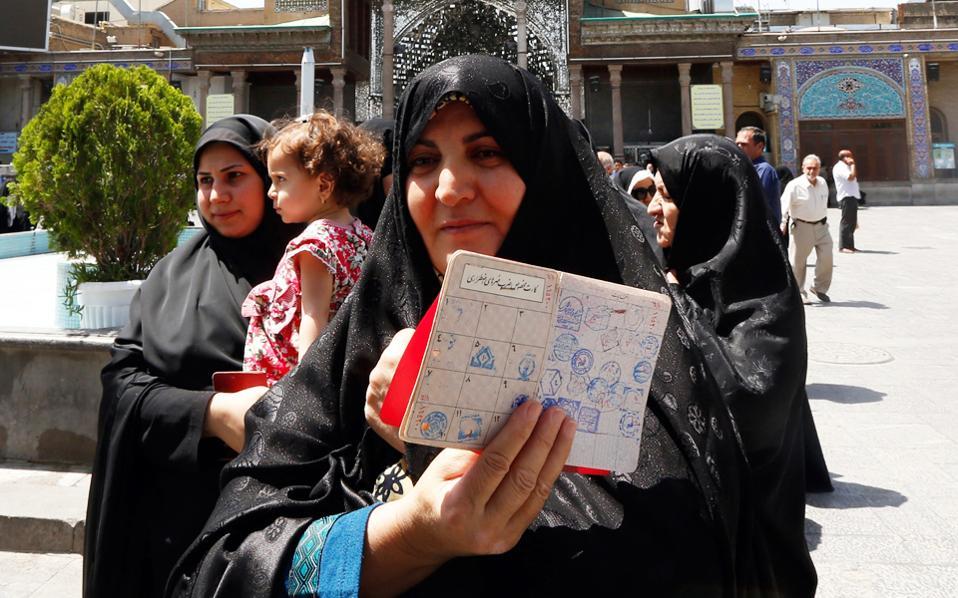 Τα στοιχεία ταυτότητας επιδεικνύει η Ιρανή της φωτογραφίας, καθώς περιμένει να ψηφίσει έξω από εκλογικό κέντρο του Ρέι, νοτίως της Τεχεράνης.
