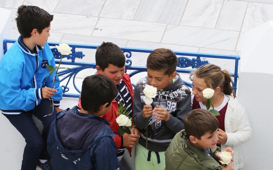 Παιδιά του Δημοτικού κρατούν λευκά τριαντάφυλλα για να τιμήσουν τον εκλιπόντα.