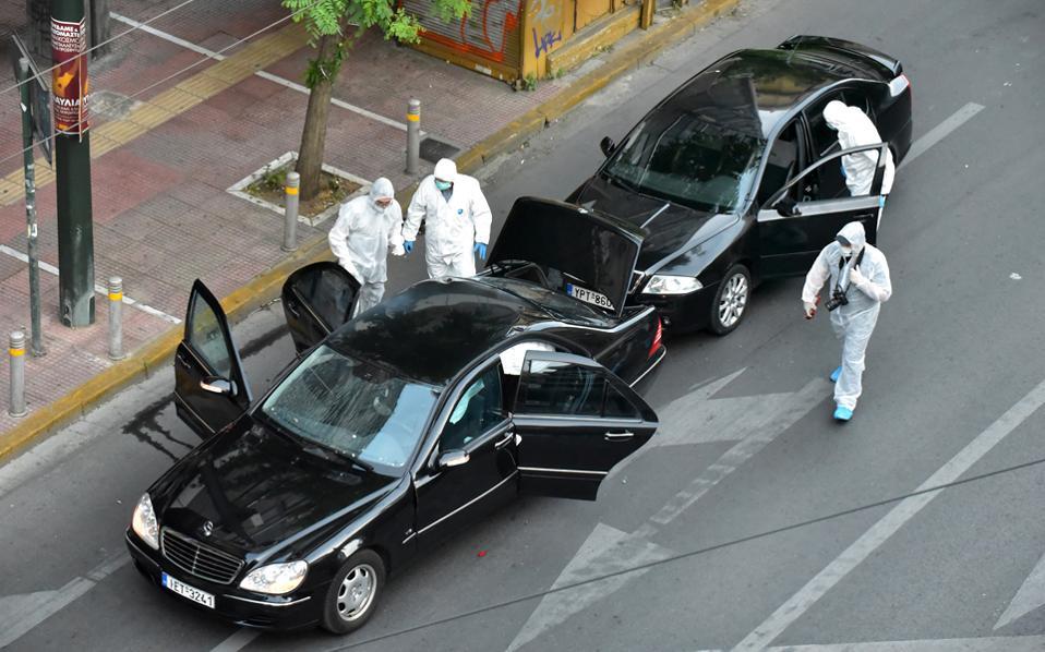Άνδρες του Εγκληματολογικού συλλέγουν στοιχεία. Το αυτοκίνητο στο οποίο επέβαινε ο Λ. Παπαδήμος και τα υπολείμματα του φακέλου βρίσκονται στα εγκληματολογικά εργαστήρια για διερεύνηση.