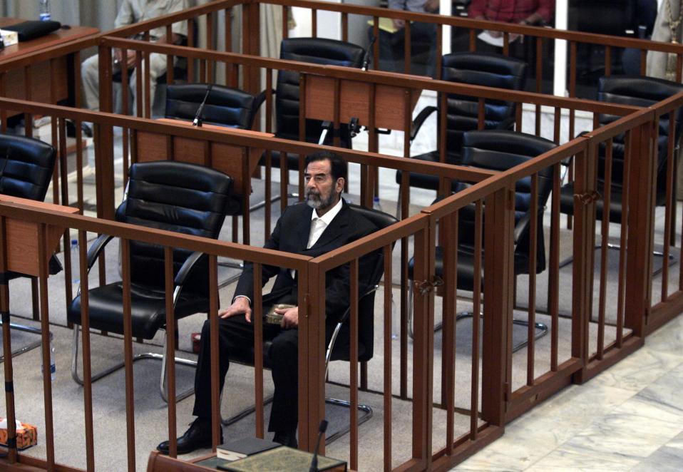 Ο πρώην Ιρακινός πρόεδρος Σαντάμ Χουσέιν ακούει τις κατηγορίες που του απαγγέλει ο δικαστής Ραούφ Αμπντέλ-Ραχμάν κατά τη διάρκεια της δίκης του στη βαριά οχυρωμένη «Πράσινη Ζώνη» της Βαγδάτης, το 2006. Ο δικαστής έκρινε ένοχο τον πρώην παντοδύναμο πρόεδρο του Ιράκ για δολοφονίες πολιτών, βασανιστήρια γυναικών και παιδιών και την παράνομη σύλληψη 399 ατόμων στα πλαίσια ενός κύματος διώξεων κατά των Σιιτών τη δεκαετία του '80, φέρνοντας τη δίκη του Χουσείν σε ένα νέο στάδιο. (AP Photo/Marco Di Lauro)