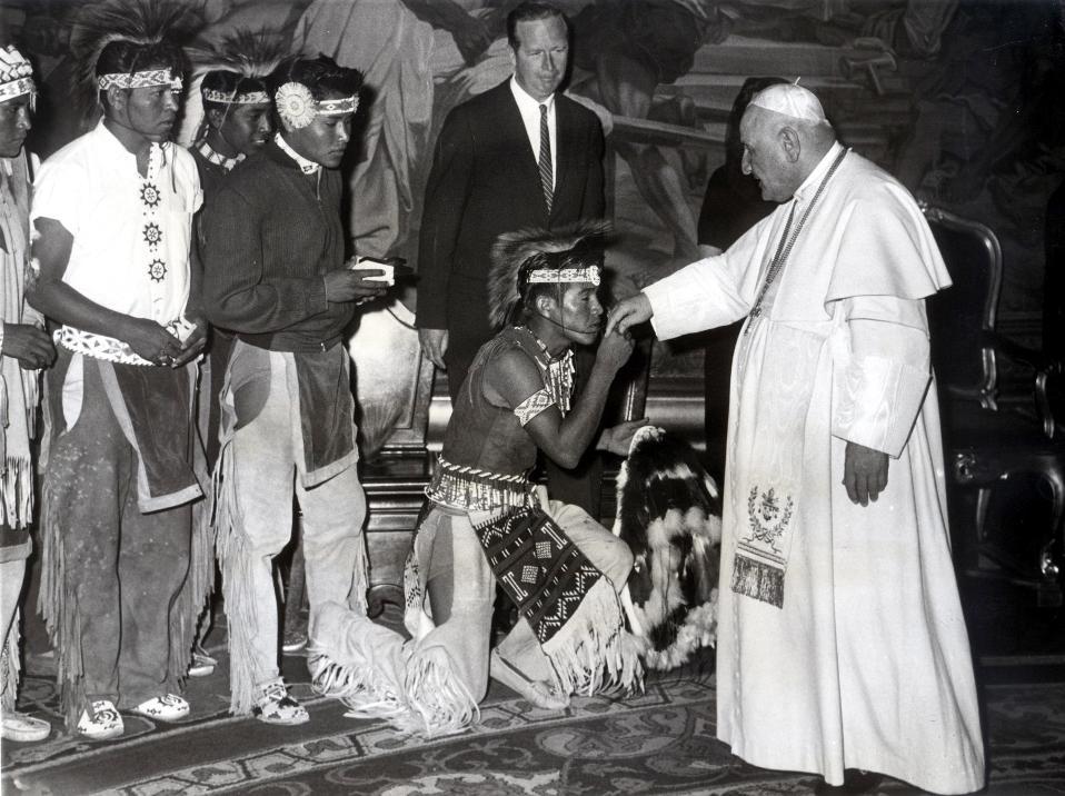 Ένας Αμερικανός Ινδιάνος Απάτσι σκύβει και φιλά το χέρι του Πάπα Ιωάννη ΚΓ' κατά τη διάρκεια επίσημης επίσκεψης της αντιπροσωπείας των Απάτσι στο Βατικανό, το 1961. (AP Photo/STR)