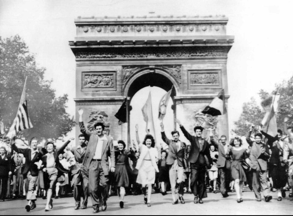 Πολίτες του Παρισιού πανηγυρίζουν μπροστά από την Αψίδα του Θριάμβου για την άνευ όρων παράδοση της ναζιστικής Γερμανίας, κραδαίνοντας σημαίες των συμμαχικών χωρών, το 1945. Την προηγούμενη μέρα, η γερμανική στρατιωτική ηγεσία υπέγραψε την παράδοση της χώρας στην πόλη Ρενς της βόρειας Γαλλίας. (AP Photo)