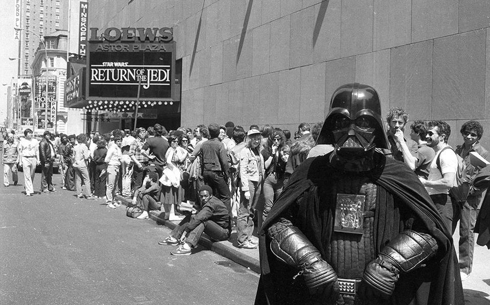 Ο φανατικός οπαδός της σειράς ταινιών επιστημονικής φαντασίας «Ο Πόλεμος των Άστρων», Ντάνι Φιτζέραλντ, ντυμένος με στολή του ήρωα των ταινιών, Νταρθ Βέιντερ, στέκεται μπροστά από κινηματογράφο στην Τάιμς Σκουέρ της Νέας Υόρκης, όπου πλήθος ανθρώπων περιμένει στην ουρά, για να παρακολουθήσει την πρεμιέρα του τρίτου μέρους της πρώτης τριλογίας της κινηματογραφικής σειράς, «Η Επιστροφή των Τζεντάι», το 1983. (AP Photo/Dave Pickoff)