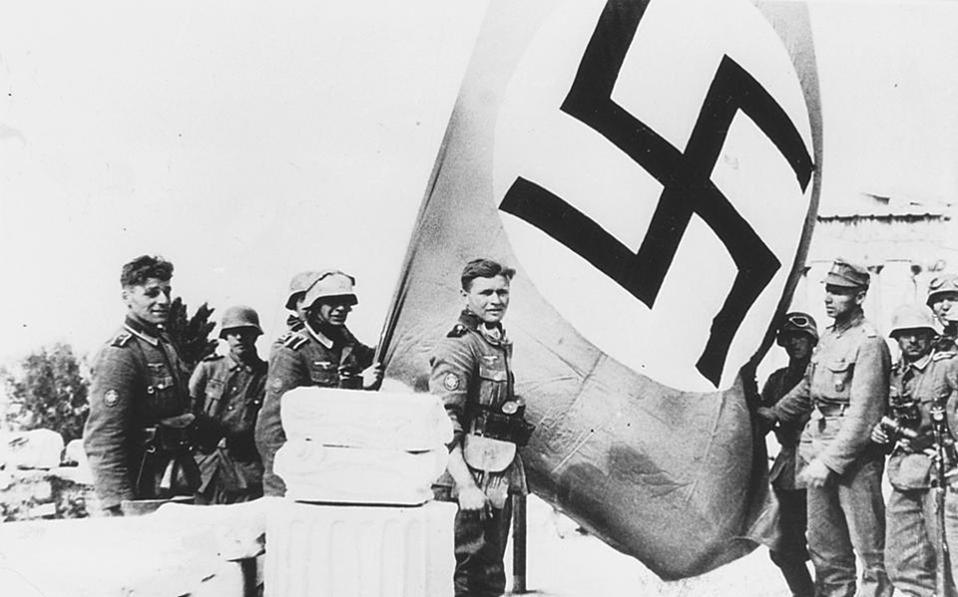 Δύο νεαροί φοιτητές, ο Μανώλης Γλέζος και ο Λάκης Σάντας, 19 ετών αμφότεροι, πρωταγωνιστούν σε μία από τις πρώτες αντιστασιακές πράξεις στην κατεχόμενη Ελλάδα και Ευρώπη, κατεβάζοντας τη σημαία της Ναζιστικής Γερμανίας από τον ιστό του ιερού βράχου της Ακρόπολης, το βράδυ της 30ης προς 31η Μαΐου, το 1941. (Φώτο: kathimerini.gr)