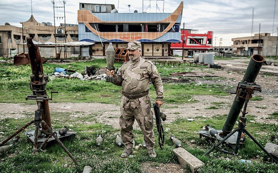 Κρατώντας έναν όλμο στα χέρια του, αυτός ο άνδρας ποζάρει μπροστά από κατασχεμένα όπλα των τζιχαντιστών.