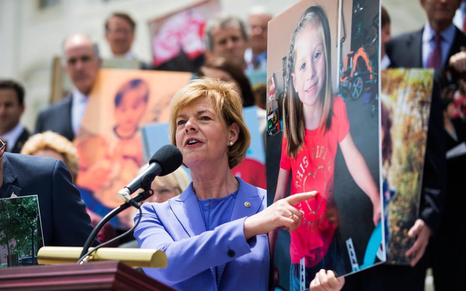 Δημοκρατικοί γερουσιαστές κρατούν φωτογραφίες παιδιών που θα χάσουν την ασφαλιστική τους κάλυψη.
