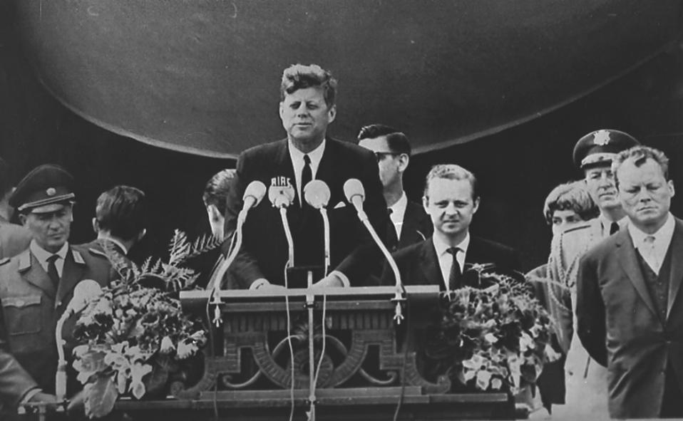 """Ο Αμερικανός πρόεδρος Τζον Φιτζέραλντ Κένεντι εκφωνεί τον διάσημο λόγο του στο Δυτικό Βερολίνο, ο οποίος περιέχει τη μνημειώδη φράση """"είμαι ένας Βερολινέζος"""", το 1963. Με τον λόγο αυτό, ο οποίος εκδηλώθηκε στο απόγειο του Ψυχρού Πολέμου, ο Κένεντι εξέφρασε τη στήριξη του στους κατοίκους της Δυτικής Γερμανίας, δυο χρόνια μετά την ανέγερση του Τείχους του Βερολίνου, του κατ' εξοχήν συμβόλου της ψυχροπολεμικής διχοτόμησης της Ευρώπης. (AP Photo)"""