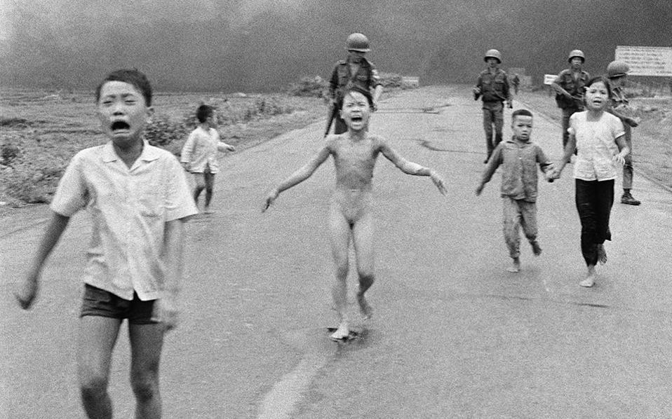 Νοτιοβιετναμέζοι στρατιώτες της 25ης Μεραρχίας ακολουθούν μικρά τρομοκρατημένα παιδιά, τα οποία τρέχουν τρομαγμένα μετά από ρίψη βομβών ναπάλμ εναντίον πιθανών θέσεων των ανταρτών Βιετκόνγκ, το 1972, η οποία τελικώς έπληξε Νοτιοβιετναμέζους στρατιώτες και πολίτες. Στο κέντρο της φωτογραφίας, η οποία βραβεύτηκε το βραβείο Πούλιτζερ, βρίσκεται η τότε 9χρονη Κιμ Φουκ, η οποία καθώς έτρεχε για να σωθεί από τις φλόγες των εμπρηστικών βομβών, έβγαλε τα φλεγόμενα ρούχα της και αποθανατίστηκε γυμνή στη φωτογραφία που έγινε σύμβολο της φρίκης του πολέμου του Βιετνάμ. (AP Photo/Nick Ut)