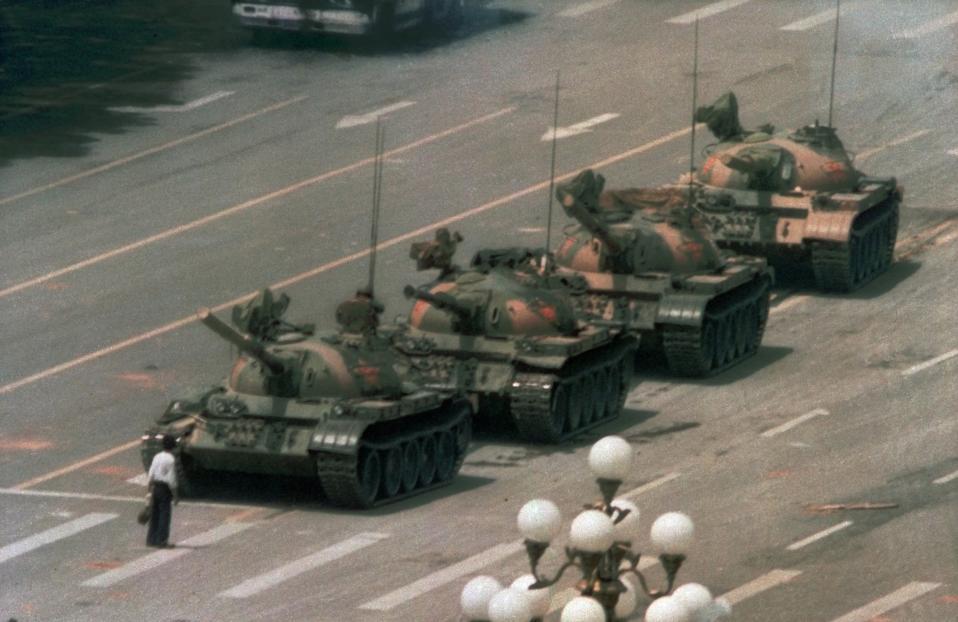 Ένας Κινέζος άνδρας προσπαθεί να σταματήσει την πορεία των τεθωρακισμένων οχημάτων στην πλατεία Τιέν Αν Μεν του Πεκίνου, το 1989. Ο διαδηλωτής, ο οποίος ζητούσε τον τερματισμό της βίαιης καταστολής της φοιτητικής εξέγερσης υπέρ της δημοκρατίας, απομακρύνθηκε τελικώς από δύο άνδρες και τα τανκς συνέχισαν την πορεία τους. Ο κινεζικός στρατός κατέστειλε με ιδιαίτερη σκληρότητα τις φοιτητικές κινητοποιήσεις εκείνης της χρονιάς, αφήνοντας νεκρούς αρκετές εκατοντάδες διαδηλωτές. (AP Photo/Jeff Widener)