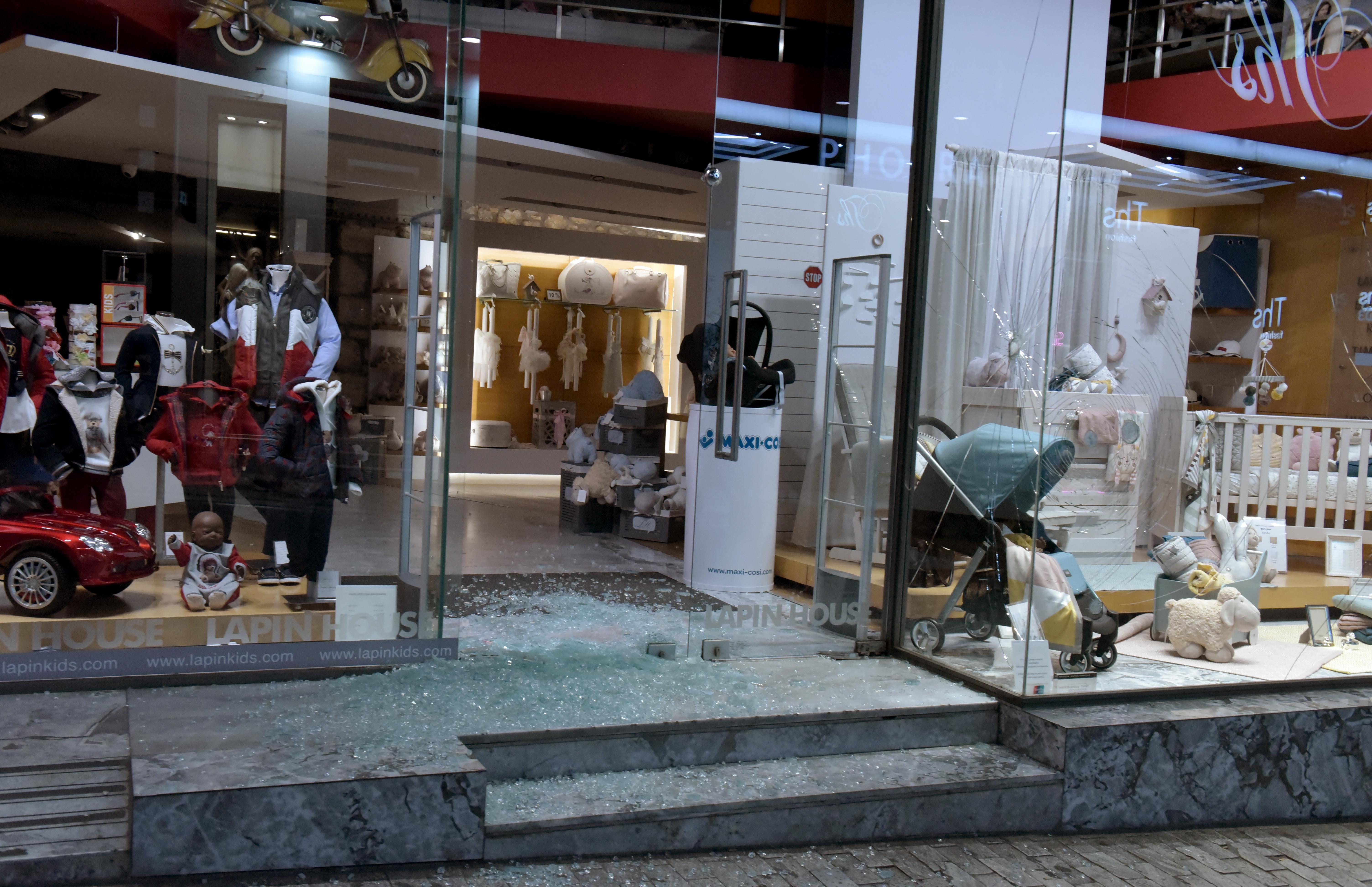 Η ομάδα των αντιεξουσιαστών έσπασε βιτρίνες και εισόδους αρκετών  καταστημάτων κοντά στο σταθμό Μοναστηράκι. 405c2b582d6